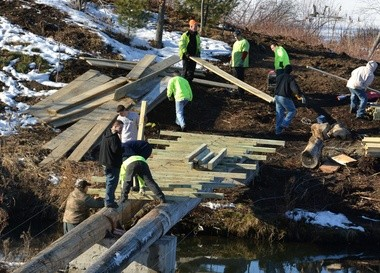 A community service crew from the Western Massachusetts Correctional Alcohol Center helps out earlier this month with a footbridge project on park land off South Branch Parkway near Watershops Pond, also known as Lake Massasoit, in Springfield. Northern Tree Service is funding the footbridge and a mulch walking trail at the East Forest Park site, and aiding with the cleanup of downed trees and limbs from the 2011 tornado.