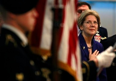 U.S. Sen.-elect Elizabeth Warren, D-Mass., right, places her hand on her chest during the playing of the national anthem while looking toward an honor guard during ceremonies to commemorate the opening of the Massachusetts National Guard Joint Force Headquarters at Hanscom Air Force Base, Mass., Thursday, Dec. 13, 2012. The ceremonies also celebrated the 376th birthday of the National Guard. (AP Photo/Steven Senne)