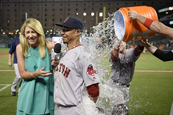 Boston Red Sox' Mookie Betts, center, gets doused with water as he gets interviewed after a baseball game against the Baltimore Orioles, Tuesday, May 31, 2016, in Baltimore. Betts hit three home runs as the Red Sox won 6-2.