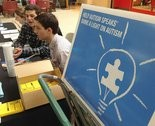 "Volunteers man the table for the Western New England Walk Now for Autism Speaks event Saturday at the Holyoke Mall at Ingleside. The event featured ""Light IT UP Blue"" a sale of blue light bulbs to kick off April as Autism Awareness Month with April 2nd as World Autism Day. (DAVE ROBACK /THE REPUBLICAN)."
