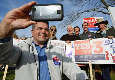 John Ribeiro, chair of Repeal the Casino Deal ballot committee, takes a photograph with fellow casino opponents at Mittineague Congregational Church in West Springfield, Nov. 4, 2014.