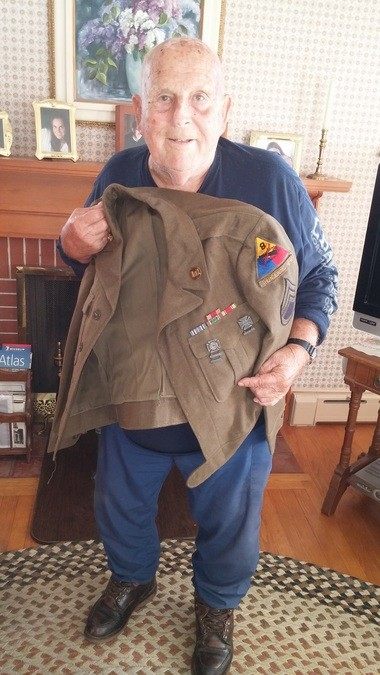 Eddie Neilson displays Eisenhower jacket from his World War II service in the Army.