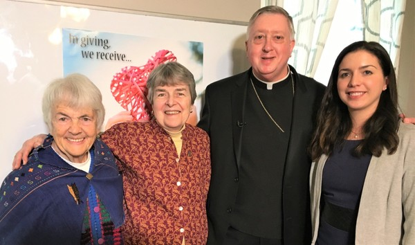 From left, Sisters of St. Joseph Jane Morrissey and Catherine Homrok, both founders and residents of Gray House, Bishop Mitchell Rozanski, and Teresa Spaziani, Gray House executive director, pose in front of the poster for the 2018 Annual Catholic Appeal at Gray House on Jan. 30.