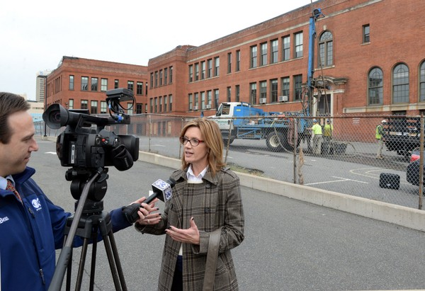 Kelley Tucky, MGM vice president of public affairs - East Coast, speaks with Hugh Zietlan from CBS 3 outside the old Howard Street School in Springfield Wednesday as crews from Seaboard Geotechnical Environmental Drilling perform soil testing at the site of what will be the parking garage for MGM Springfield.