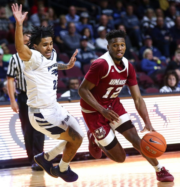 Massachusetts' Carl Pierre (12), shown driving to the hoop in a game against Nevada, had five 3-pointers in UMass' thrilling 79-78 win over Providence on Friday. (AP Photo/Chase Stevens)