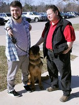 Nick Ackerman with service dog Troy and dog trainer Cheryl Carlson, of Cher Care Kennels, in St. Johns, go over some verbal commands.