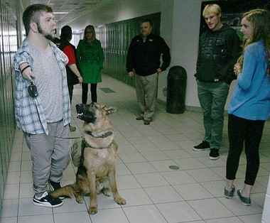 Nick Ackerman and his service dog Troy stop to talk to friends in the hallway.