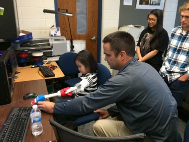 Adam Zavislak helps Maili work with her new hand while students Alex Dolce (left) and Alex Koth look on.