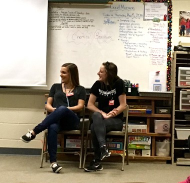 Paityn Wedder and Katelyn Johnson watch the video with the students in a fourth-grade classroom.