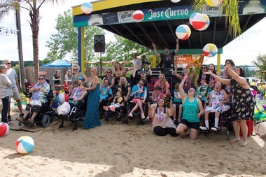 A group of residents from Oliviaas Gift throw beach balls in the air at their annual Summer Beach Bash fundraiser. Oliviaas Gift is a local nonprofit organization that works to build residential housing for young adults with disabilities.