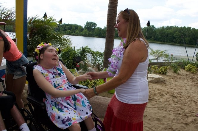Olivia Henrickson dances with her mom, Kelly, at the annual Summer Beach Bash fundraiser in honor of Henrickson's birthday. The annual fundraiser is hosted by OIivia's Gift, a nonprofit organization that works to build residential housing for young adults with disabilities.