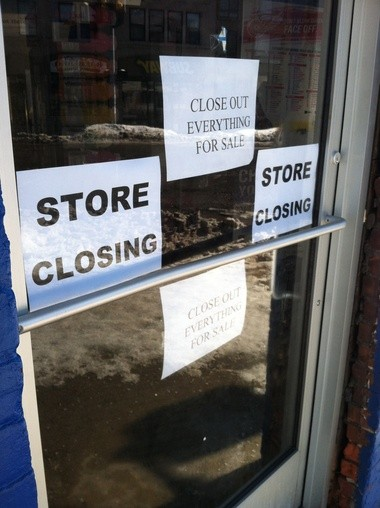 Blue Front's door and window is covered with store closing signs.