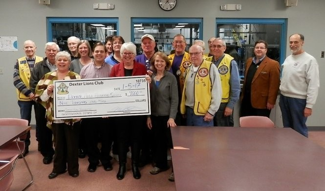 Beverly Hill, President of the Dexter Area Historical Society, and other Board members gratefully accept a check from Dexter Lions Club, whose president is Dennis Berry.