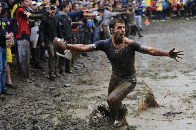 A Sigma Alpha Epsilon member sticks out his tongue and his arms as he scores a touchdown against Phi Psi in the Mud Bowl Oct. 19. Brianne Bowen | The Ann Arbor News