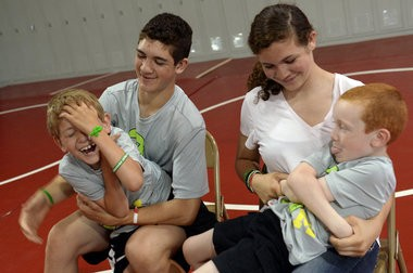 From left, Hunter Gandee, 14, holds his brother Braden, 7, while their youngest brother Kellen, 6, sits in his 13-year-old sister Kerragen's lap as they all goof around in the wrestling room at Bedford Junior High School on June 4, 2014. Hunter is planning a 40-mile walk carrying Braden, who has Cerebral Palsy, on his back, to raise awareness for the disorder. Melanie Maxwell | The Ann Arbor News