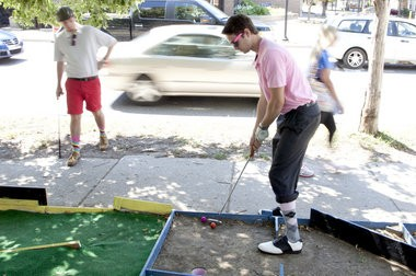Kevin McDonald, right, putts as traffic passes by at Dusty Clubs Mini-Golf in Ann Arbor on Thursday, Aug. 14, 2014. McDonald and his roommate, Jordan Hammock, left, made the mini-golf course in their front yard. Patrick Record | The Ann Arbor News