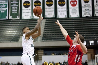 Eastern Michigan graduate transfer Anali Okoloji shoots over a Ball State defender at the Convocation Center in Ypsilanti, Mich., on Jan. 7, 2015. Ball State defeated Eastern Michigan, 60-59. Patrick Record | The Ann Arbor News