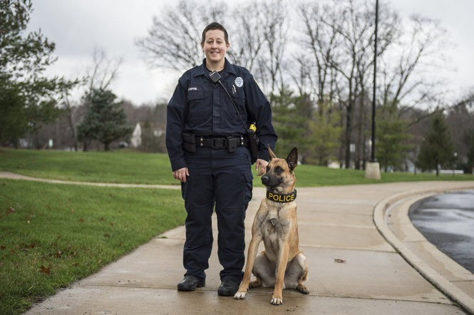 Officer Bridget Bofysil poses for a photo with Nitro outside of the Student Center on EMU campus, Tuesday, December 22, 2015, in Ann Arbor, Mich. (Junfu Han | The Ann Arbor News)