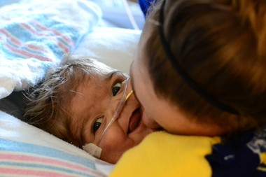 Micah smiling after getting a kiss from his mother, Jennifer Canvasser in 2012 at C.S. Mott's Children's Hospital.