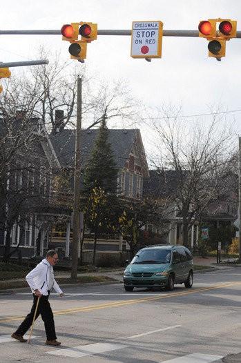 A pedestrian crosses Huron Street in Ann Arbor using a HAWK signal. Ypsilanti will have a similar signal on Michigan Avenue.