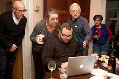 Sabra Briere looks over the shoulder of her campaign manager as he checks the polls for the 1st Ward race at her home Tuesday night.