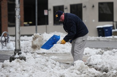 A man shovels heavy melting snow at the corner of W. Huron and N. Ashley streets in downtown Ann Arbor in this file photo.