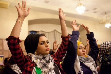 Michigan PhD student and instructor of political science Imaan Ali, left, raises her hands with other students in agreement with a speaker Tuesday night.