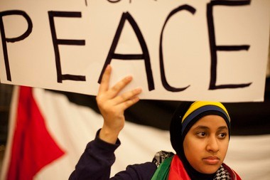 "Michigan sophomore Noran Alsabahi holds a ""Divest for Peace"" sign during Tuesday's meeting."