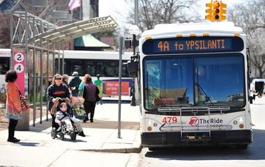 Passengers prepare to board a bus in downtown Ann Arbor.