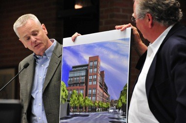 Project architect Mike Siegel, left, and developer Dan Ketelaar hold up a rendering of 618 South Main at an Ann Arbor City Council meeting when the project was approved.
