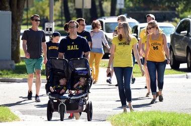 University of Michigan fans walk toward Michigan Stadium before Saturday's game against Minnesota.