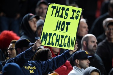 """A Michigan fan holds up a sign that reads """"This is not Michigan"""" as the clock ticks down in the second half against Rutgers at High Point Solutions Stadium in New Jersey on Saturday, October 4, 2014."""