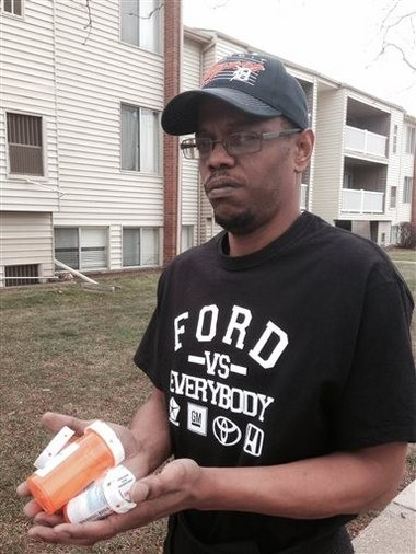 Tonocca Scott, 40, of Ypsilanti, stands outside his apartment building with prescription drugs for back pain. Scott blames Dr. Aria Sabit for a botched back surgery. The Detroit-area doctor is charged in federal court with fraud. Sabit pleaded guilty to billing insurers for faulty procedures and misleading patients about how he planned to fix their spines. (