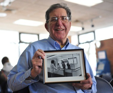 Ann Arbor resident Clark Charnetski, former chairman of the Michigan Association of Railroad Passengers, poses for a portrait inside the Amtrak station on Depot Street in Ann Arbor on Feb. 13, 2015, holding a photo of him standing at the counter on the day the station opened in January 1983.