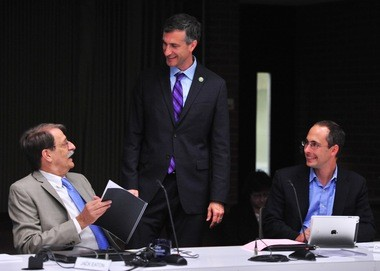 Mayor Christopher Taylor, standing, chats with Jack Eaton, left, and Chuck Warpehoski before the start of the Ann Arbor City Council's meeting on July 20, 2015.
