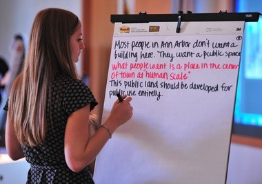 Kayla Coleman, systems planning analyst for the city of Ann Arbor, records public comments on Library Lot development proposals at a meeting on Oct. 22, 2015.