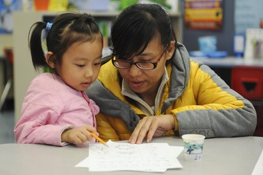 Hua Tian works with her daughter Tammy Wang, 5, in a kindergarden class during National African American Parent Involvement Day at Bryant Elementary School on Feb. 9, 2015.