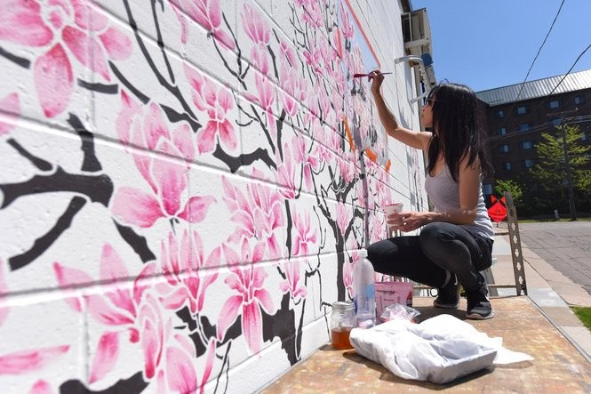 Cate Tinsley, an artist from New York and creator of Olive Leaf Stencils, uses her stencils to make a magnolia tree mural on Jefferson Street near Main Street in Ann Arbor on May 18, 2016.