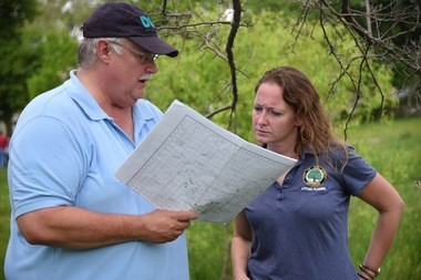 Dan Hamel of the Michigan Department of Environmental Quality and Jennifer Lawson, the city of Ann Arbor's water quality manager, look over a map in West Park on May 25, 2016.