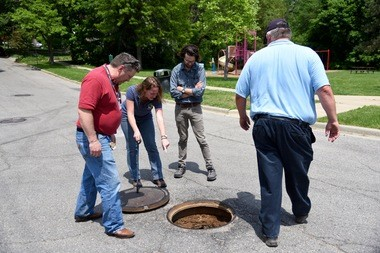 Jennifer Lawson, the city of Ann Arbor's water quality manager, shows Kevin Lund, Alex Rosen and Dan Hamel a sanitary sewer manhole on Eighth Street next to Slauson Middle School where there's evidence of groundwater seeps on May 25, 2016. In the background is the playground area of Waterworks Park where dioxane has been discovered in shallow groundwater.