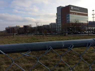 The proposed development site along Broadway Street and Maiden Lane, currently a field surrounded by a chain-link fence, as it looked on Nov. 27, 2016. In the background is the University of Michigan's Kellogg Eye Center.