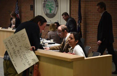 "Ann Arbor resident Roger Kuhlman speaks to City Council Member Sumi Kailasapathy, while holding a sign reading: ""No sanctuary city for criminal illegal aliens in Ann Arbor. I believe in the rule of law."""