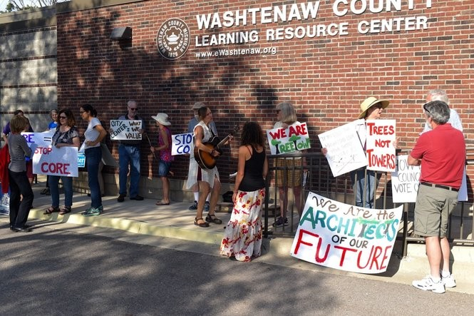 Protesters demonstrate outside the Washtenaw County Learning Resource Center before an Ann Arbor City Council candidate forum on July 25, 2017.