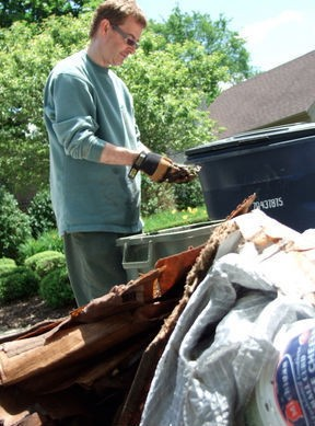 Larry Fingerle sifts through the remains of his basement after stormwater runoff flooded his home after a storm in June 2010.