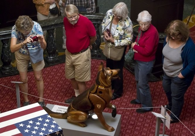 """ArtPrize-goers look at James Mellick's entry """"Wounded Warrior Dogs"""" at Amway Grand Plaza in Grand Rapids on Friday, Oct. 7, 2016. (Cory Morse 