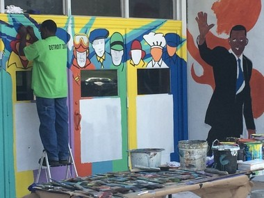 A Life Remodeled volunteer paints a mural Thursday on the exterior of Cody High School in Detroit. (Michael Wayland | MLive Detroit)
