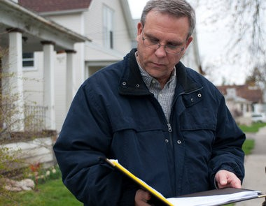 Rick Brzezinski, county treasurer, checks his list of homes to visit for Bay City home owners who are delinquent on property taxes on March 31, 2012.
