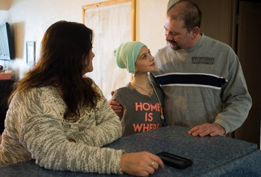 Pam Christie watches Pete Christie hug his daughter, Cassidy, 10, who is battling cancer Wednesday, Feb. 18, at home in Bangor Township.