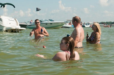 Mike Hilderbrand throws a ball to Jenna Kolka, 9, in the water Saturday, Aug. 15, at Boaters Beach in the Saginaw Bay.