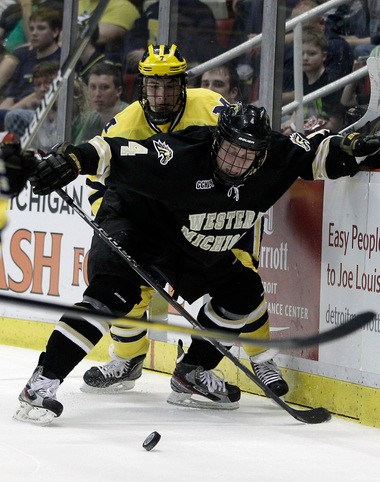 Western Michigan defenseman Garrett Haar (4) and Michigan forward Phil Di Giuseppe (7) battle for the puck during a past game. WMU released Haar from the program Friday.